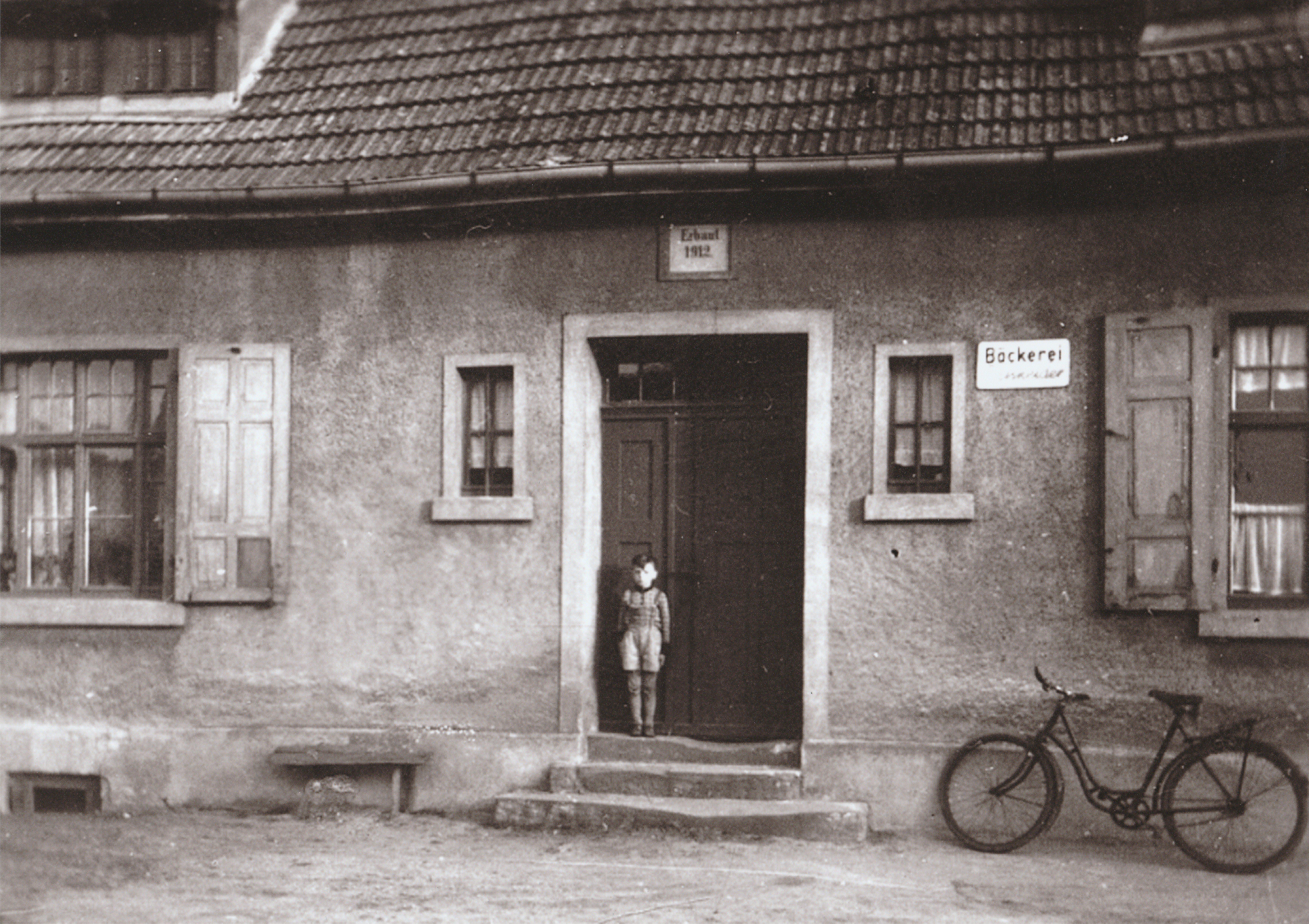 Hier ist das Erbauungsdatum der Bäckerei 1912 zu erkennen. Die Aufnahme enstand 1960 - In der Tür steht Gerhard Schneider, Sohn des damaligen Bäckermeisters Rudolf Schneider